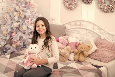 Morning before christmas. New year holiday decorations. Girl kid in bedroom with toys. Happy new year. Ask if the person has a wish list. Small child celebrate new year at home decorated interior