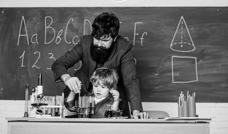 son and father at school. Wisdom. Back to school. Pharmacy and chemistry theme. solution in research laboratory. Genetic research. small boy with teacher man. You educate a man.