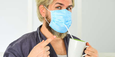 Serious about hygiene. Guy in mask drink tea coffee using straw. Cover mouth and nose with mask and make sure no gaps between face and mask. Totally protected. Wearing mask protect from coronavirus