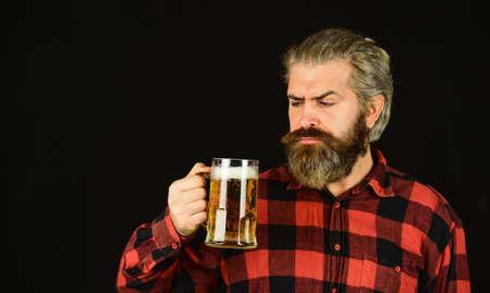 tasting beverage for pub. trying a new beer. brutal hipster drink beer. mature man hold beer glass. mug of alcohol beverage. confident bartender. barman in bar. resting at pub. Cheers. sport bar