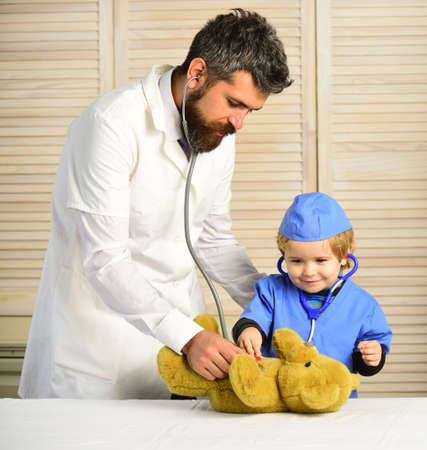 Vet and little assistant examine teddy bear. Health and childhood Stock fotó