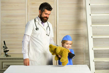 Man with beard and boy in medical gowns hold bear