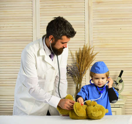 Father and kid with attentive faces playing doctor.