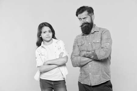 Oh, please no. Man and child yellow background. Bearded man and little girl keep arms crosses. Hipster man and small kid in casual style. Father and daughter relationship. Fatherhood changes man