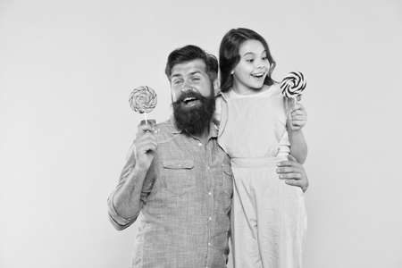 Daughter and father eat sweet candy. Bearded man and cute sweet baby. Loving daddy and small girl eating lollipop. Summer vacation. Happy holidays. Sweet childhood. When children seem hard to please