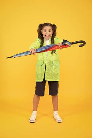 Waterproof concept. Match your raincoat with umbrella. Schoolgirl wear raincoat. Small schoolgirl wear water resistant clothes for rainy day. Cute schoolgirl feel protected for spring weather