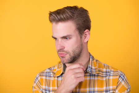 Handsome caucasian man with unshaven face skin and stylish hair yellow background, skincare