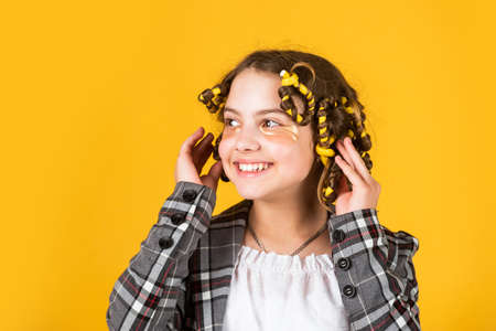 Create beautiful hairstyle. Gorgeous hairstyle. Happy child. Hairdresser salon. Perfect beauty. Girl with curlers and hair clips in her hair on yellow background. Little girl curlers around her hair