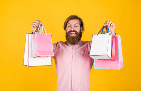 Taking two. prepare for holidays. best sale offer. happy bearded man with present pack. cheerful brutal hipster hold gift. paper shopping bag. birthday surprise at party. man with package Stock fotó