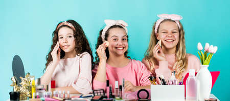 three happy girls at hairdresser. friendship and sisterhood. family bonding time. childhood happiness. retro kids put on makeup. skin care cosmetics for children. beauty and fashion