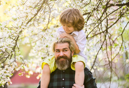 Cheerful father playing with his child in park. Handsome dad with his little cute son. enjoy bloom and nature together. happy family day. spring is coming. just have fun. love concept