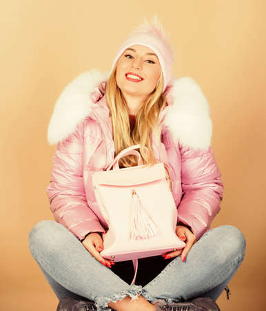 ready to go. girl in puffed coat. faux fur fashion. flu and cold season. Leather bag fashion. happy winter holidays. woman in beanie hat with backpack. warm winter clothing. shopping