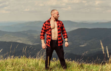 muscular male. cowboy in hat outdoor. sexy macho man in checkered shirt. man on mountain landscape. camping and hiking. countryside concept. farmer on rancho. travelling adventure. hipster fashion