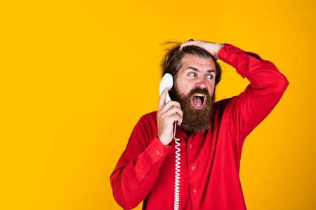 oh no. bearded man wear red shirt. casual male answering call. concept of conversation. man secretary or assistant speak on retro phone. brutal man with telephone. communication. copy space 免版税图像