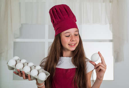 preparing from eggs. happy child wear cook uniform. chef girl in hat and apron. kid cooking food in kitchen. choosing a career. little helper with eggs. culinary and cuisine. happy childhood