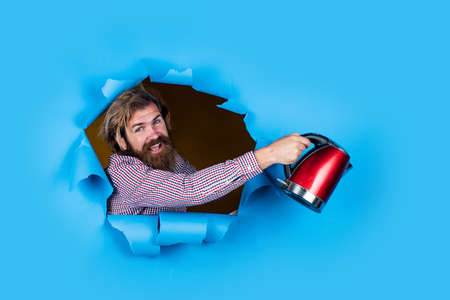 Modern technology make life easier. brutal bearded man with electric kettle. happy man torn blue background. mature guy using a kettle in the kitchen to boil water for tea or coffee
