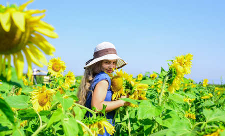 kid wear straw summer hat. child in field of yellow flowers. teen girl in sunflower field. concept of summer vacation. rich harvest and agriculture. happy childhood. Supporter of environment