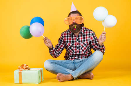 fun and happiness concept. happy man holding colorful helium balloons. hipster smiling happily. having fun on party. prepare for holidays. Event manager poses with festive accessory