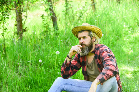 Ecology concept. Green field in summer. Countryman sit on green meadow. protect green environment. Agriculture farmer rest after day work. Worker in rural farm. farmer hold plant