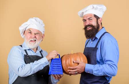 hard to cook. halloween pumpkin recipe. using grater. Chef men cooking. cheerful men prepare food. autumn pumpkin cooking. mature senior bearded men in kitchen. professional restaurant cook Stock fotó - 154911548