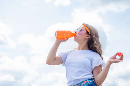 wearing funny party glasses. kid fashion style. teenage girl on sky background outdoor. hipster kid. happy childrens day. happy childhood. smiling child drink water from bottle. copy space