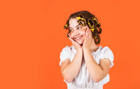 Styling tips. Teen hobbies. Hairstyling. Beautiful girl Curling Hair Using Curlers. Daughter with curlers on her head laughing. Hairdresser salon. Adorable child hairdo. Female beauty routine