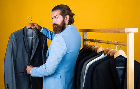 my choice. professional male sartor with jacket on hanger. perfect design. tailor man has fashionable look. Elegant suits hang in row. Mens clothes on hanger. mature man looking for jacket Reklamní fotografie
