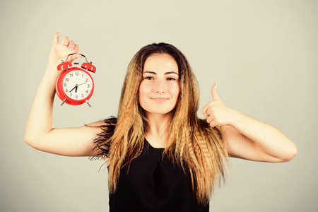 Daylight saving time. Watch repair. Punctuality and discipline. Practice of advancing clocks. Change time zone. Pretty girl managing her time. Time management. Woman hold vintage alarm clock
