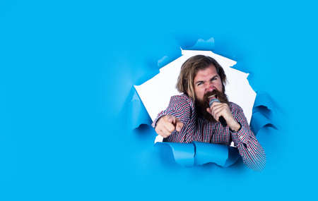 you are the next. place for copy space. hipster singing a song. music. happy bearded man on blue background. mature event manager hold microphone. have some fun. birthday party singer