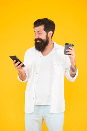 happy mature bearded man enjoy reading good news on phone while drinking morning coffee, joy and pleasure