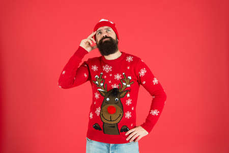 thoughtful hipster touch beard. lost in thoughts. focused on choosing a gift. should i wear warm clothes. what weather is it today. bearded man knitted accessory. its christmas time.what to present