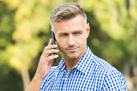business approach. communication in modern life. agile business. mature unshaven man shirt. male speaking on mobile phone outdoor. handsome guy working on the go. male has conversation