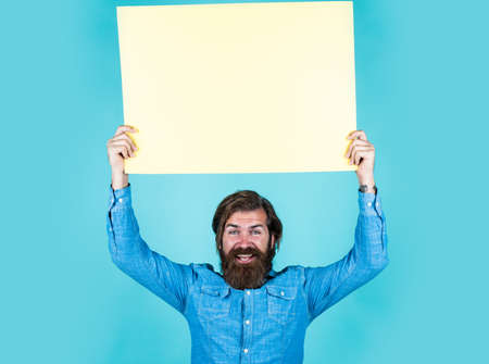 Above all in service. happy bearded man with empty paper sheet. barbershop service. concept of advertisement. brutal man with beard and moustache. search for a job. place for copy space