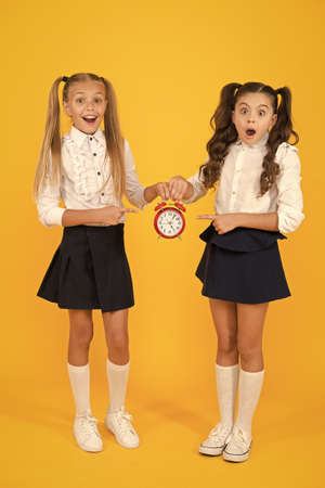 It is time. School schedule. Schoolgirls and alarm clock. Children school pupils. Knowledge day. School time. Surprised shocked kids hold alarm clock counting time. Latecomer will be punished