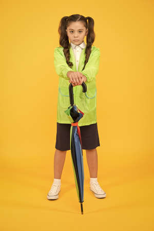 accessory for fall season. autumn kid fashion. dry and comfortable in rainy weather. small girl in raincoat with umbrella. schoolgirl waterproof raincoat. feel protected and happy