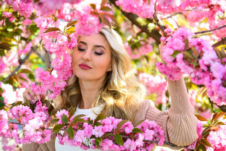 I love gardening. female flower perfume. beauty of spring nature. attractive woman with makeup. girl has long curly blonde hair. healthy beauty. pink sakura flowers. natural beauty and cosmetics