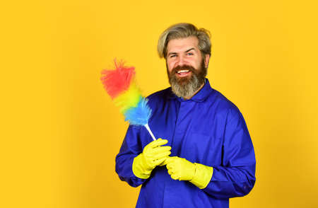 cleaning and home concept. Male Sweeping with small duster broom. cleaning service. housekeeping business. Cleaning the apartment. man use duster. hipster holding the cleaning tool. Unfair situation