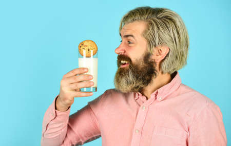 happy farmer eat dessert. bearded man drink useful milk with pastry. cookie and glass of milk. man love bakery. bakery goods concept. his favorite food. enjoying freshly baked pastries Stock Photo