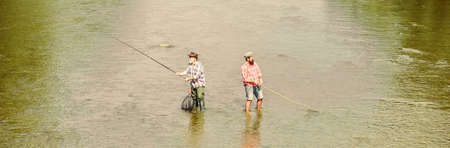 Summer weekend. Happy fisherman with fishing rod and net. Hobby and sport activity. Fishing together. Men stand in water. Fishing is much more than fish. Male friendship. Father and son fishing