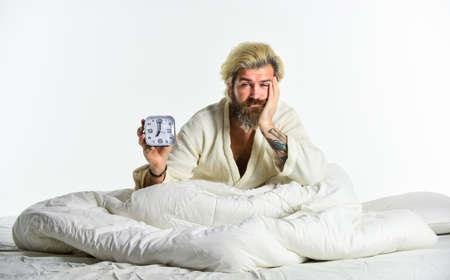 Bearded man with alarm clock. Awakening. Sleep complex biological process that helps process new information, stay healthy and feel rested. Stressed man alarm clock. Sleepy guy and alarm clock in bed Imagens