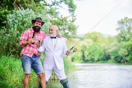 outdoor picnic. summer family weekend. father and son fishing. mature man fisher celebrate retirement. two fishermen with fishing rods. hobby and sport activity. retired businessman. male friendship Stock fotó