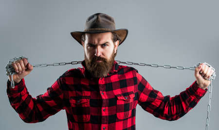 Do not give up. chained up in chains. bearded man has aggressive look. express his strength. male power and masculinity. mature hipster break chain. fetter. brutal man in cowboy hat with chain