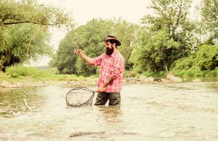 Fishing is astonishing accessible recreational outdoor sport. Bearded fisher catching trout fish with net. Fishing hobby. Fishing provides that connection with whole living world. Find peace of mind