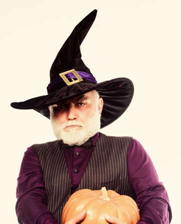 Stargazer in holiday costume. Traditional food. bearded man ready for halloween party. happy halloween. mature man magician in witch hat. evil wizard hold orange pumpkin. the highway to hell.