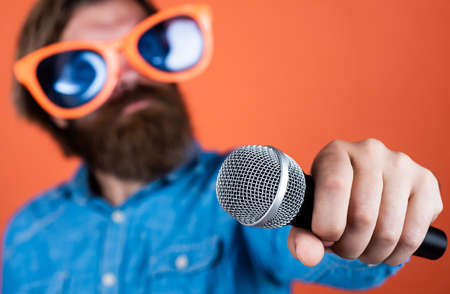 party goer. hipster man with beard wearing glasses. music concept. have a happy holiday. have fun on party. male singer singing song in microphone. selective focus. celebrate the anniversary Stock Photo