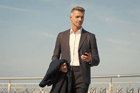 Businessman formal outfit with smartphone. Modern life concept. Boss on way to office. Use phone while walking. Urban style. Regular working day. Charismatic man blue sky background. Phone call