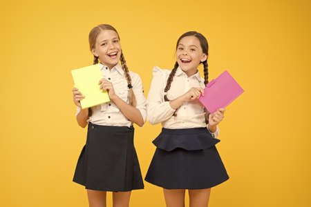 Beyond the Book. little girls in school uniform. cheerful classmates with workbook. dictionary notebook. Get information. reading story. childrens literature. kids learning grammar. back to school