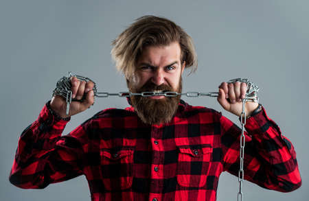 Live life. man in captivity. concept applicable for business. man tearing heavy steel chain by teeth. conceptual symbol of freedom. male fashion. strong man with chains. problem solving