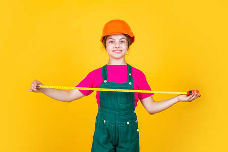 kid repairing home. happy childhood. self-retracting metal tape measure. girl using a measuring tape. construction worker with tape measure. Cute kid as a construction worker. I think I can fix it