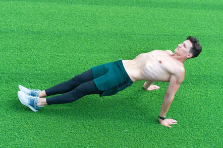 Reverse plank helps strengthen lower back, man exercising outdoors